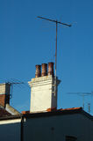 Chimney. Roof detail, old chimney made of bricks, four televison antennas Stock Photos