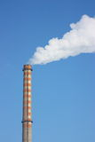 Chimney. With white smoke on a clear blue sky background Royalty Free Stock Photography