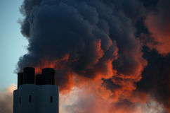 Chimney. The illumination by the setting sun gives the vapor an ominous impression, like of volcano smoke stock images