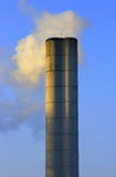 Chimney. Large chimney sent clouds of steam into the blue sky royalty free stock image