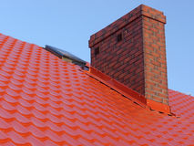 Chimney. Closeup of red roof metal covering with brick-made chimney Royalty Free Stock Photography