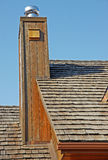 Chimney. A chimney clad in wood siding stands tall against a cedar shake roof Royalty Free Stock Photos