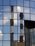 Chimney. Factory chimneys reflecting in the mirror windows Royalty Free Stock Images