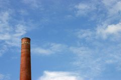Chimney against blue sky. Old brick chimney against blue sky with clouds Royalty Free Stock Photos