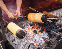Chimney cakes typical sweet of Budapest. Kurtos kalacs or Chimney Cakes roll spinning over hot coals at a market stand,the typical sweet of Budapest,Hungary Stock Photography
