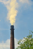 Chimney, a cloud of smoke in the sky. Yellow cloud of smoke arises from the chimney in a blue sky. leaves and branches of a tree on the left, summer Stock Photography