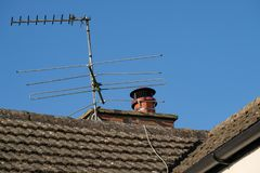Newly fitted chimney cowl fitted to a chimney pot seen with a TV antenna. royalty free stock image