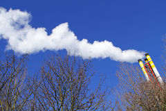 Chimney emitting smoke against a blue sky Royalty Free Stock Photos