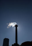 Chimney exhausting steam in blue sky Stock Photo