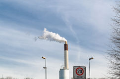 Chimney factory with smoke against the blue sky Stock Photos