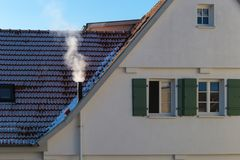 Chimney fumes on rooftop. Of buildings on a sunny winter day in south germany historical city royalty free stock photo