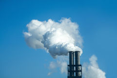 Chimney with industrial smoke against blue sky Stock Photo
