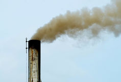 Chimney. Industrial chimney or smokestack emitting gases visible against blue sky Stock Image