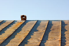 Chimney on an obsolete tinny roof. Against the blue sky Stock Photos