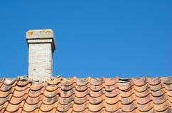 Chimney at an old broken tiled roof Stock Image