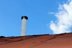 Chimney pipe over the old tinny roof Royalty Free Stock Images