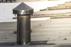 Chimney pipe from stainless steel on the roof of the house. Rust stock photography
