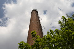 Chimney pollution. Chimney under white cloudscape in summer times Royalty Free Stock Photography
