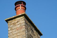 Chimney pot and cowl seen on a house chimney stack. The bird cowl is seen fitted to prevent birds from nesting in the chimney which is used to heat the house in Stock Photography