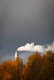 Chimney producing smoke on a dark sky backdrop Stock Image