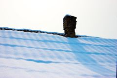 Chimney in red bricks with white snow on roof. Detailed view fro. M Sweden stock photography