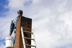 Chimney repair. Brick mason on a ladder repairing damaged chimney Royalty Free Stock Image