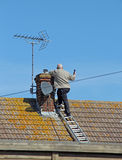 Chimney Repair. This photo shows a male making repairs to the top of a chimney. This photo could be used for backgrounds and to illustrate the safe way to access Royalty Free Stock Image