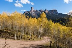 Chimney Rock and Court House Mountain stands above an aspen grove along Owl Creek Pass road. View of Chimney Rock and Court House Mountain from Owl Creek Pass royalty free stock photos