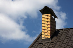 Chimney on a roof. Of house over blue sky with clouds Royalty Free Stock Photos