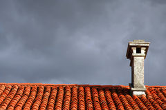 Chimney on the roof. A chimney on a roof of a house with sky covered with clouds stock photography