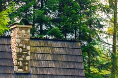 Chimney on the roof of a rural house close up, decorative stone Stock Photos