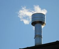Chimney on the roof with smoke coming out from the boiler Royalty Free Stock Photos