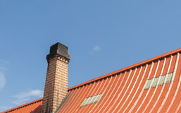 Chimney with roof tiles, Orange on blue sky background Stock Images