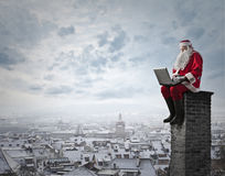On the chimney. Santa Claus sitting on top of a chimney Royalty Free Stock Image