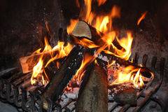 Chimney Scene. Fireplace with burning wood on an iron grill royalty free stock photography
