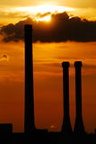 Chimney silhouettes in sunset. A sunset with chimney silhouettes and a dark cloud stock photography