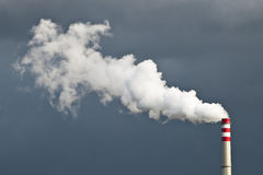 Chimney Smoke. White smoke from the chimney in front of the dark cloudy sky Stock Photos