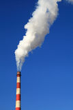 Chimney Smoke. Chimney with white smoke on a clear blue sky background Royalty Free Stock Photo