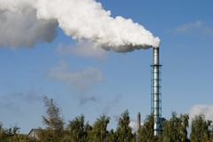 Chimney and Smoke. Chimney and white smoke on a claer blue sky Royalty Free Stock Photo