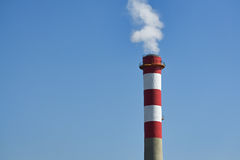 Chimney and smoke. Chimney of a factory with white smoke and clear blue sky Royalty Free Stock Photography