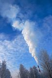 Chimney smoke in forest. Scenic view of chimney emitting clouds of white smoke above forest Stock Photo