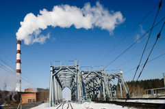 A chimney smoke over railroad bridge Stock Photography