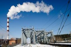 A chimney smoke over railroad bridge Stock Photography