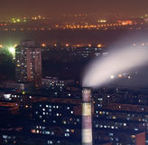 Chimney with smoke in residents area at night Royalty Free Stock Photo