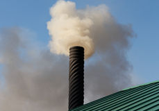 Chimney Smoke Stack. An angled view of a black textured chimney on a green steel roof emitting smoke against a clear blue autumn sky Royalty Free Stock Photo