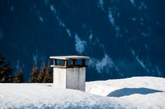 Chimney on snow covered roof. Of skiing hut in Montafon, Austria Stock Photo