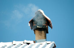 Chimney on the snow covered roof Stock Photos