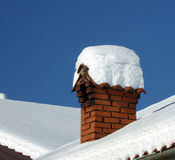 Chimney on the snow covered roof Royalty Free Stock Images