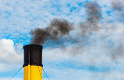 Chimney from steamboat with black smoke. Chimney from steamboat with black coal smoke, yellow and black chimney with cloudy clear sky Royalty Free Stock Photography