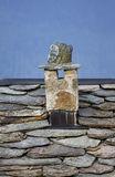 Chimney in stone. Stone chimney above the roof slate Royalty Free Stock Images